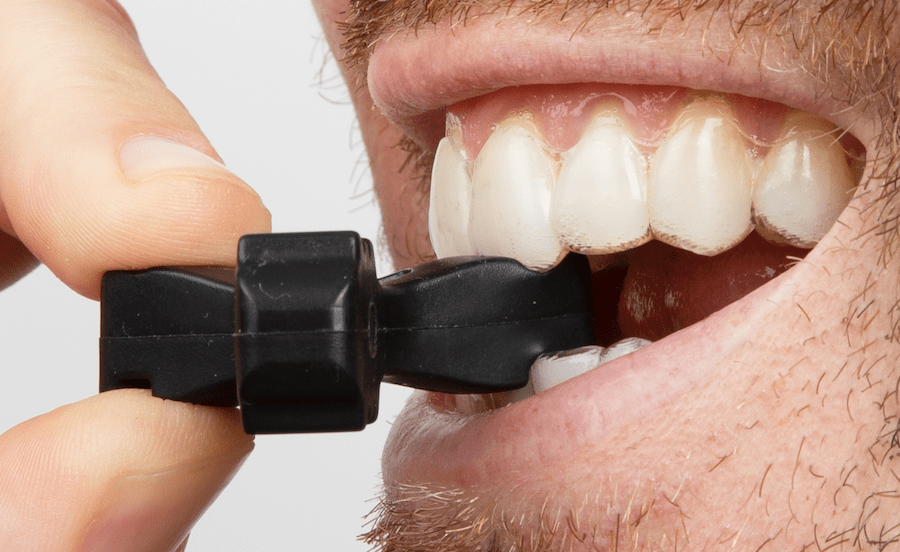 Side, close-up view of Munchies® Maintain engaged with lower central incisor